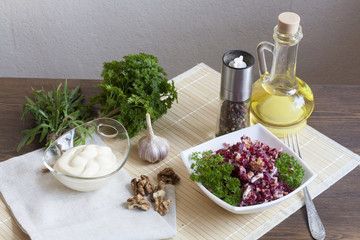 Beetroot salad with walnuts and cream sauce. Nuts, garlic, salt, pepper, herbs, boiled eggs and oil on a wooden table.