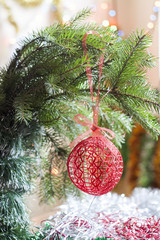 Christmas crochet woven ball in tree on colorful background bokeh among Christmas and New Year decor