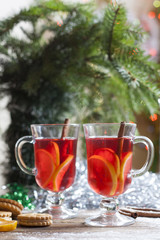 Tea with lemon, tangerines, cookies and nuts in Christmas decor with Christmas tree, nuts and apples on colorful background bokeh