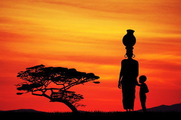 African woman with child in African landscape