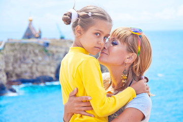 Mother kissing daughter. Happy family resting at beach. Mother and daughter, tender, soft blur