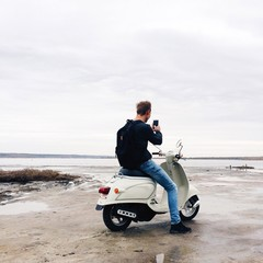 hipster man make phone photo on motocycle on the sea beach