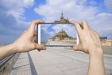 Girl taking pictures on mobile smart phone in Mont Saint-Michel,
