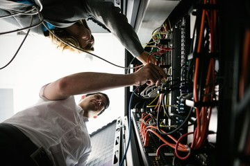 Technicians working together in server room