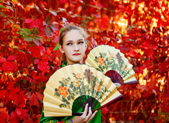 A girl holds a Chinese fan