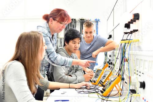 Unterricht in Elektrotechnik bei der Berufsausbildung - Gruppe von Auszubildenten und einer Lehrerin // Teaching in Electrical Engineering - group of trainees and a teacher