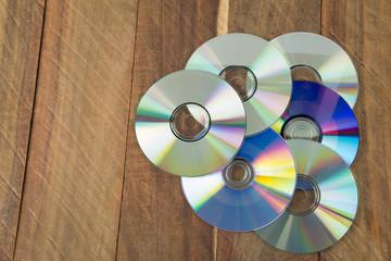 Discos compactos en fondo de madera rústica.