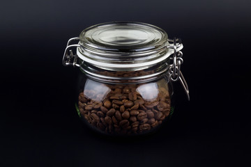 Coffee grains in glass jar on a black background