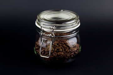Coffee grains in a glass jar on a black background