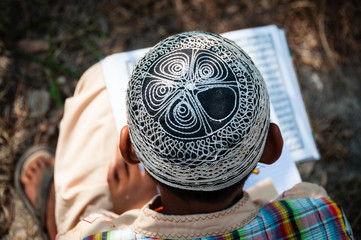 Sitting Boy with hat reading in Quran book