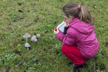Bimba con tablet che fotografa i funghi