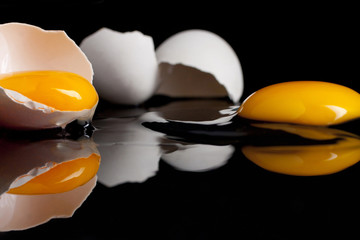 Twee gebroken eieren op een zwarte spiegelplaat, waarvan de dooiers nog heel zijn en het eiwit langzaam wegloopt uit de eierschaal.