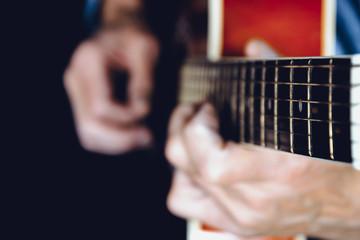 Blurred image of hands playing a guitar