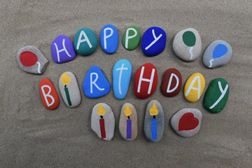 Happy Birthday message on colored stones over the sand