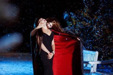 Beautiful female vampire in long pallium is biting her victim