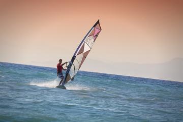 Windsurfen in Rhodos Griechenland. Mann surft im blauen Meer vor rötlichem Himmel, Insel im Hintergrund.