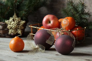 Christmas balls with mandarin oranges and apples on the table
