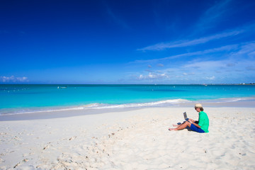 Young man with laptop on white tropical beach
