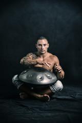 Male Drummer Drumming on Steel Drums in Studio