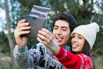 Young couple take & smile while make a photo with polaroid camer