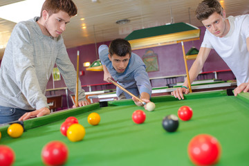 Three friends playing pool