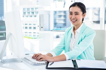 Smiling businesswoman with notes at desk
