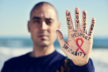 young man with a red ribbon for the fight against AIDS in his ha