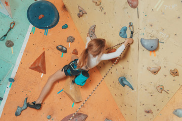 Teen girl climbing in gym