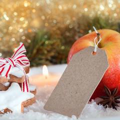 Pappschild mit Weihnachtsdekoration, Zimtsterne und Apfel