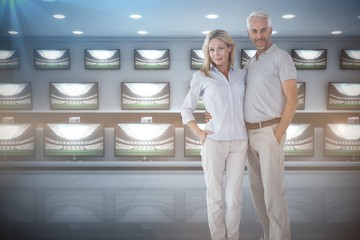 Composite image of couple standing with hands in pocket