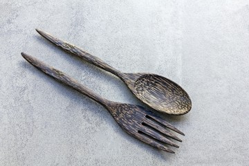 Wooden spoon and fork on tile texture