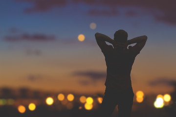 Silhouette of a man standing witf defocused city lights.