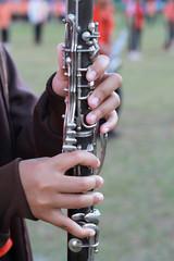 Female flutist with orchestra on sport day, school Thailand