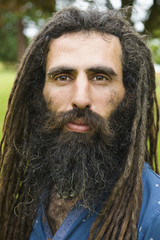 A man with long dreadlocks in a blue shirt.