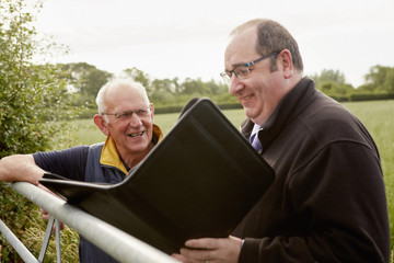 Two men standing looking over a farm gate, one with an open file and paperwork.