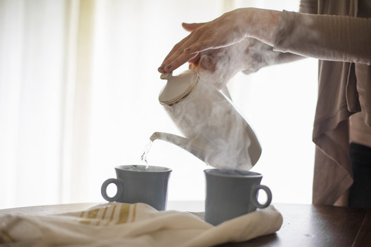 Close up of a woman pouring hot water from a coffee pot into a mug.