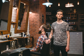 Young modern barber on his workplace with client