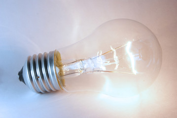 Glowing flashing light bulb lamp laying on white background