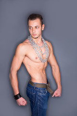 Muscular man posing, with chains