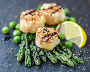 Scallops with sesame seeds , asparagus, lemon and green peas