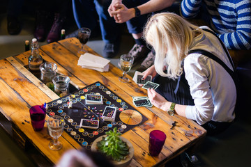 Group of young people gathered to play Alias game. Youth lifestyle, board games.