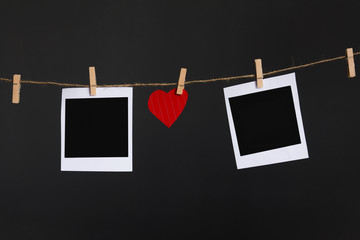 heart shape hang on rope between frame of photo