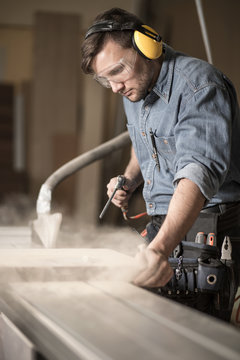 Woodworker wearing muffs and glasses