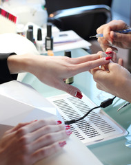 Woman in nail salon receiving manicure by beautician. Woman getting manicure at beauty salon