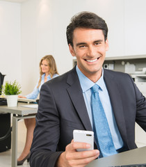 Businessman at his desk with Smartphone