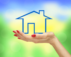 Blue house in woman hand over bright blurred nature background.