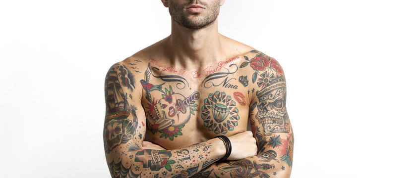Handsome and sexy tattooed man portrait with crossed arms letter