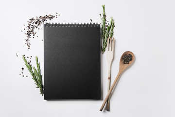Blank black cover spiral notebook on light background