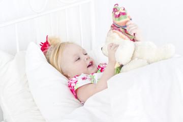 Девочка в кровати с игрушкой