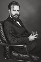 Portrait of an elegant young man with retro look sitting in an a